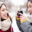 Young man taking photo of woman in winter — Stockfoto