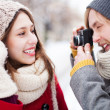 Young man taking photo of woman in winter — Stock Photo #23672869