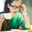 Foto Stock: Female student with books and cup of coffee