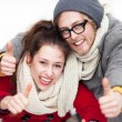 Winter couple with thumbs up - Stockfoto