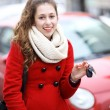 Young woman showing car key — Stock Photo