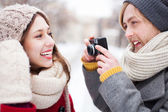 Young man taking photo of woman in winter — Stock Photo