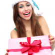 Woman in Santa hat holding Christmas present — Stock Photo