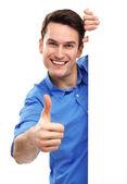 Muž s prázdnou plakát zobrazující palce — Stock fotografie