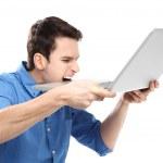homme mord un ordinateur portable dans la frustration — Photo