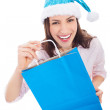 Woman in Santa hat holding shopping bag — Stock Photo