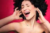 Woman with afro hair enjoying music — Stock Photo