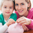 Mother and daughter with piggy bank — Foto de stock #23728643