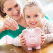 Mother and daughter with piggy bank — Stock fotografie
