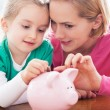 Foto Stock: Mother and daughter with piggy bank
