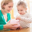 Mother and daughter with piggy bank — стоковое фото #23728847