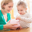 Mother and daughter with piggy bank — Foto Stock #23728847
