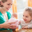 Mother and daughter with piggy bank — Foto de Stock