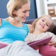 Mother and daughter reading together — Stock Photo