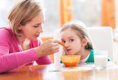 Mother feeding her daughter by spoon — Stock Photo