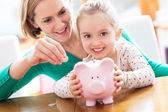 Mother and daughter with piggy bank — Стоковое фото