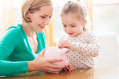 Mother and daughter with piggy bank — 图库照片
