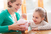 Moeder en dochter met piggy bank — Stockfoto