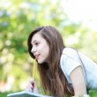 Girl lying on grass with workbook — Stock Photo #23796239