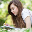 Girl lying on grass with workbook — Stock Photo