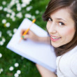 Girl lying on grass with workbook — Stockfoto