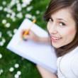ragazza sdraiata sull'erba con la cartella di lavoro — Foto Stock