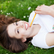 Stock Photo: Girl lying on grass with workbook