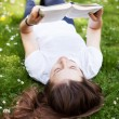 Stock Photo: Young womreading book outdoors