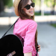 Stock Photo: Womplaying guitar in park