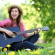 Woman playing guitar in park — Stock fotografie