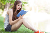 Young woman reading book outdoors — Stock Photo