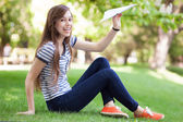 Young woman throwing paper plane — Stock Photo
