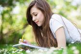 女孩躺在草地上,工作簿 — 图库照片