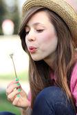 Woman blowing dandelion — Stock Photo