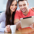 Smiling couple with digital tablet — Stockfoto