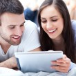 Couple with digital tablet lying on bed — Stockfoto