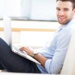 Man on sofa with laptop — Stock Photo