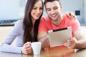 デジタル タブレットと笑みを浮かべてカップル — ストック写真