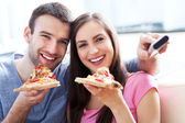 Couple with pizza and TV remote — Stock Photo
