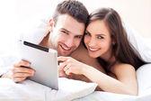 Pár s digitálním tabletu ležící na posteli — Stock fotografie