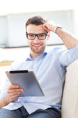 Man relaxing with digital tablet — Stock Photo