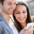 Stock Photo: Smiling couple with mobile phone