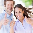 Young couple showing thumbs up — Foto Stock #26889289