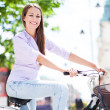 Woman riding a bike in the city — Stockfoto