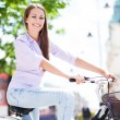 Woman riding a bike in the city — Stock Photo