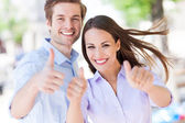 Young couple showing thumbs up — Stok fotoğraf