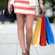 Legs and heels of woman with shopping bags — Stock Photo