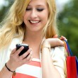 Woman with shopping bags using mobile phone — Stock Photo