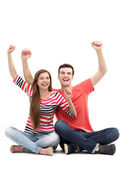 Young couple with arms raised — Stock Photo