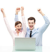 Couple in front of laptop with arms raised — Stok fotoğraf